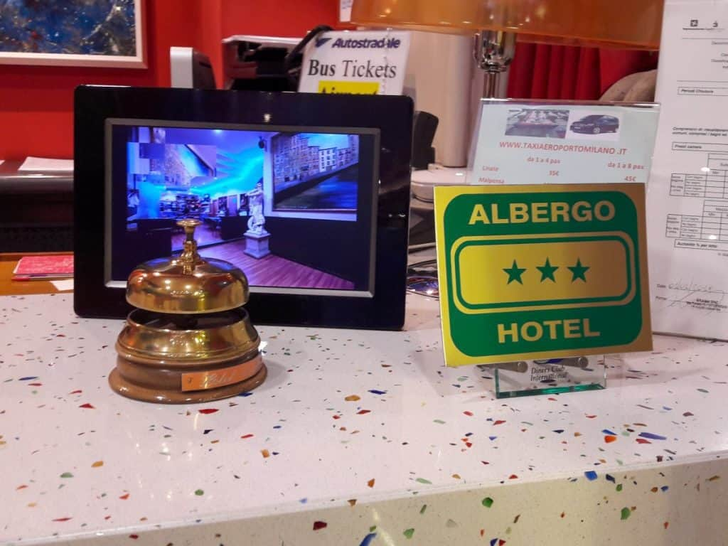 An Hotel Reception with a Green Sign and a Golden Bell
