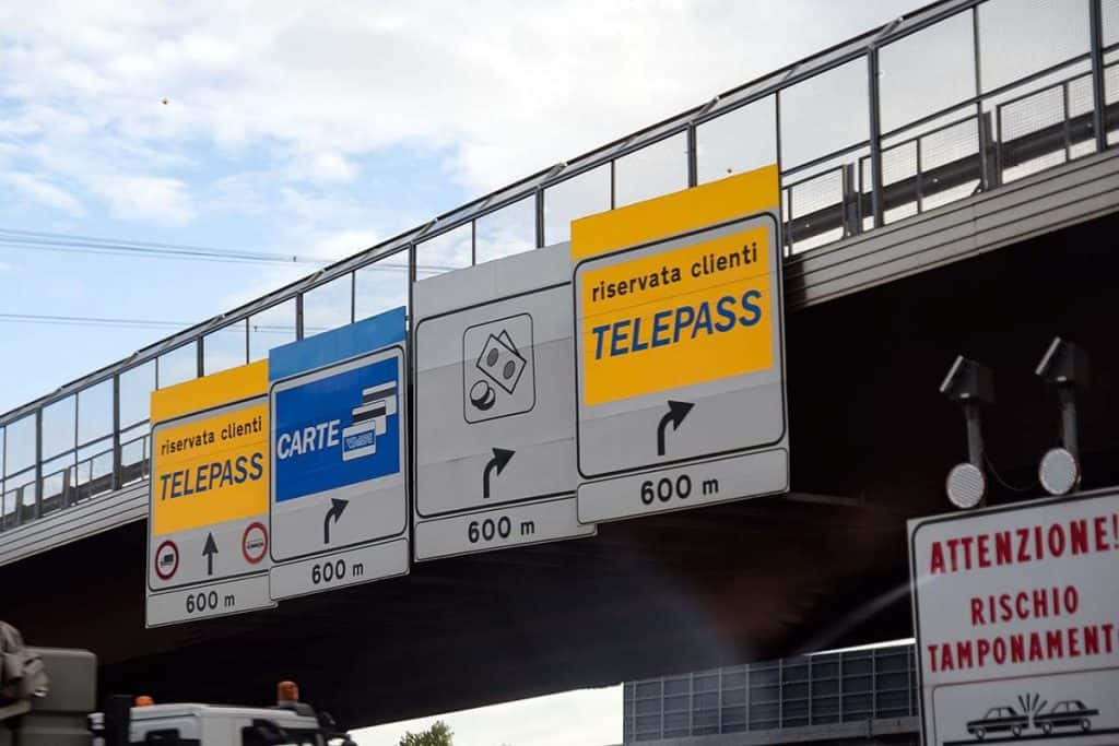 Toll road entrance with yellow, blue and white signs