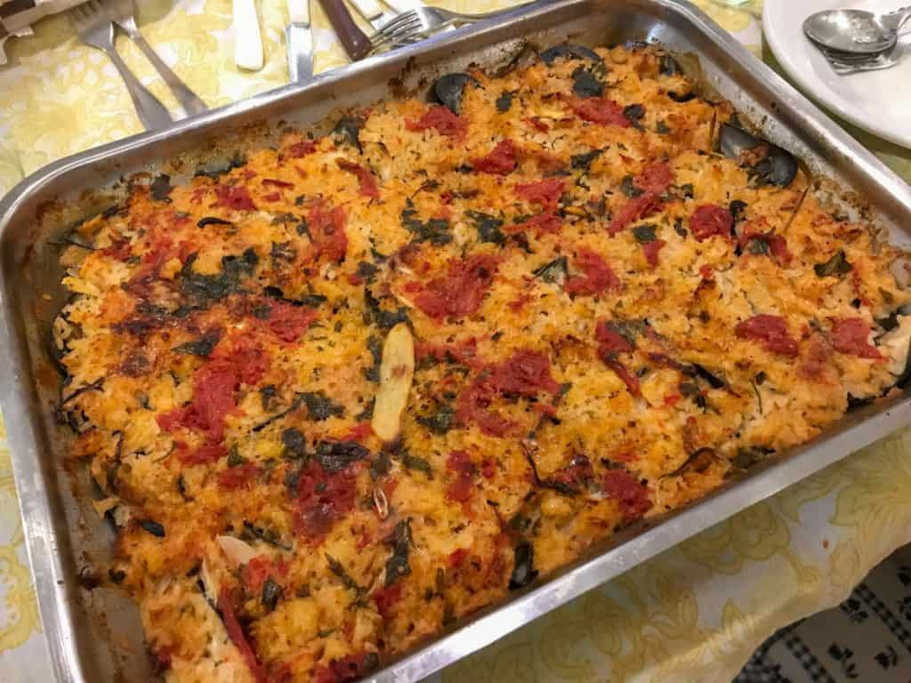 Baked Rice in a Baking Pan with Mussels, Potatoes, Onions and Tomatoes