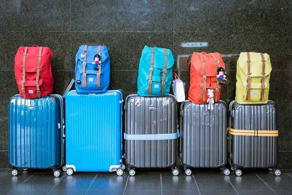 Five luggage with colored bags above them