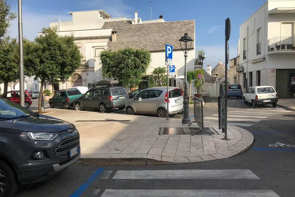 Street parking in Italy with pedestrian crossing and a blue parking sign in the middle