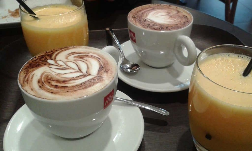 Two capuccino in a white cup and two orange juice in a glass