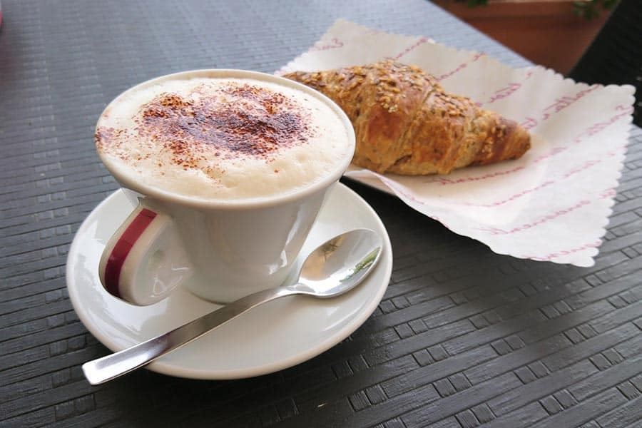 Cappuccino in a porcelain cup with a croissant