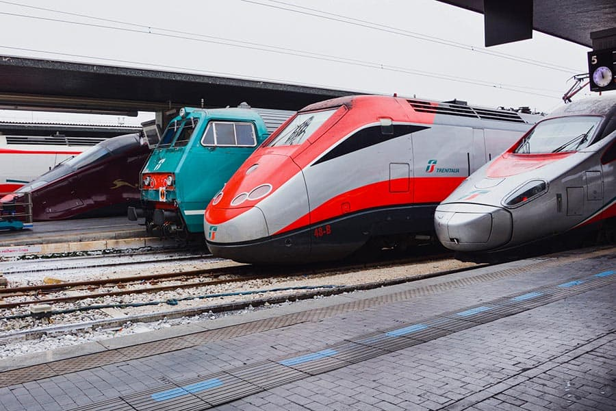 Red, silver, and green trains at an Italian train station