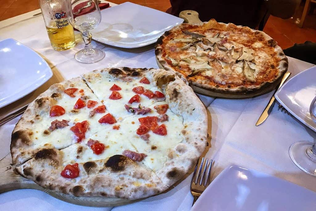 Two Italian pizzas with cheese and vegetables